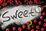 The word sweet is on a dark background next to raspberry berries