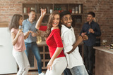 Happy interracial couple dancing at home party - 224726603