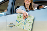 cropped shot of woman riding car with her family and holding map
