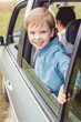 happy little kid riding car with his dad on nature and looking at camera