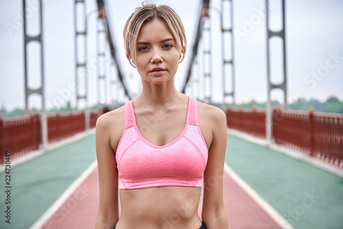 Serious about sport. Handsome young womanin sports clothing looking at camera while standing on the bridge outdoors