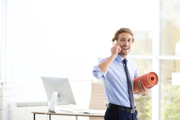 Young handsome businessman holding yoga mat in office. Space for text