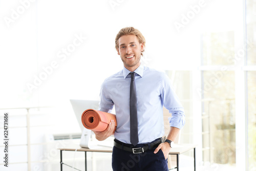 Leinwanddruck Bild Young handsome businessman holding yoga mat in office. Gym after work