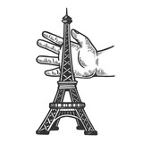 Child hand playing with eiffel tower engraving vector illustration. Scratch board style imitation. Black and white hand drawn image.