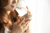 Female putting pill into glass with water and drinking it, woman's health