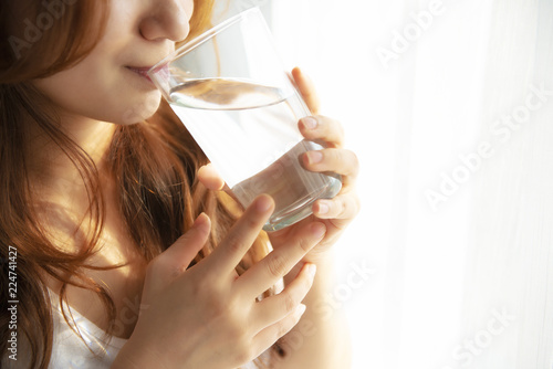 Kobieta wkłada pigułkę do szklanki z wodą i pije ją, zdrowie kobiety