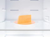 Cheese on orange plate into fridge - 224780234