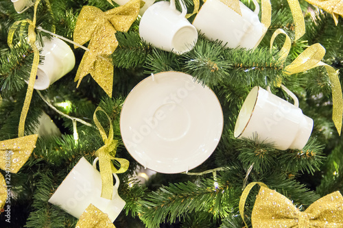 Christmas tree background and Christmas decorations. White porcelain tea cups and saucers with golden ribbons