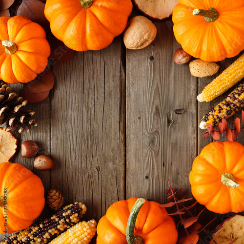 Autumn square frame of pumpkins and fall decor on a rustic wood background with copy space