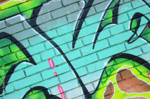 Fragment of graffiti drawings. The old wall decorated with paint stains in the style of street art culture. Colored background texture in green tones - 224793286