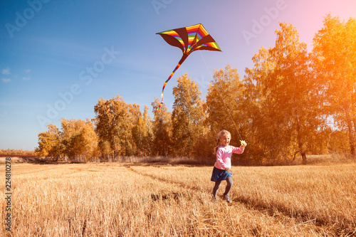Leinwandbild Motiv A small cheerful girl with blond hair smiles, enjoys nature and plays with a kite on a warm autumn sunny day in the background of a field and yellow trees.