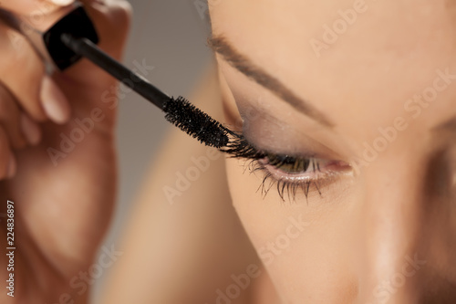 Young woman applying mascara on white background - 224836897