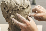 sculptor creates a bust and puts his hands clay on the skeleton of the sculpture. Close-up - 224837895