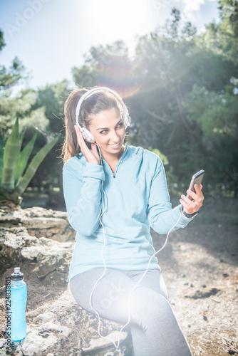 Młoda kobieta biegacz ma przerwę i słuchanie muzyki podczas biegu