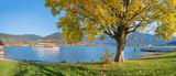 Schiffsrundfahrt auf dem Tegernsee im Herbst. Malerisches Seeufer mit herbstlichem Ahorn