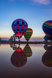 Hot air balloons taking off over lake - 224850890