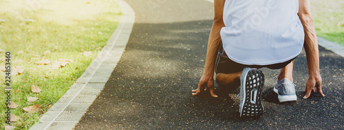 Fototapeta Athlete men in running start pose at walking way in public park. Healthy life and diet concept. Banner size with copy space.