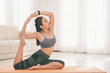 Leinwanddruck Bild - Slim sportive woman on mat stretching and training at home in peace