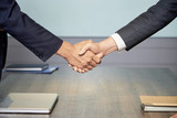 Crop side view of anonymous colleagues shaking hands above table in conference hall - 224859474