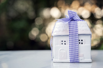 White ceramic house model on table with nature light background