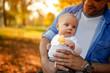 Leinwandbild Motiv Family enjoying in autumn park, cute baby boy and father