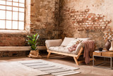 Grey wooden settee between plant and table in living room interior with rug and window. Real photo - 224881876
