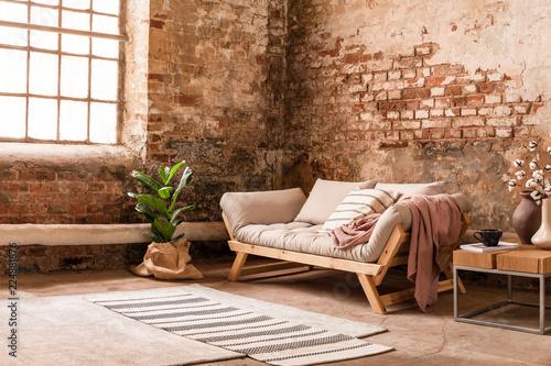 Szara drewniana kanapa między rośliną i stołem w pokoju dziennym wnętrzu z dywanikiem i okno. Prawdziwe zdjęcie