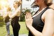 Leinwandbild Motiv Close-up view of unrecognizable woman holding hands in namaste while having morning yoga practice outdoors