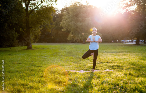 Fototapeta Yoga in the park, young woman doing tree pose vrksasana