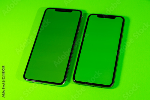 Blank green chroma key on modern smartphone mobileas hero object on bright glamorous modern neon pop green background - smartphone telephone ready for your app - 224889089