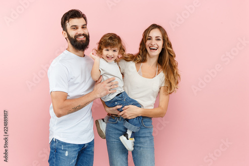 Leinwanddruck Bild A happy family on pink studio background. The father, mother and son posing together