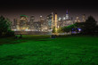 Long time exposure of New York City Manhattan downtown skyline at night viewed from Brooklyn Bridge park