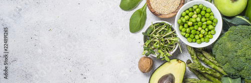 Green food assortment on light stone background.