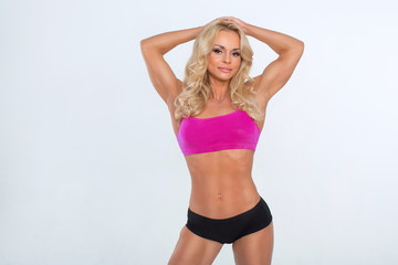 Sexy blonde with an athletic body posing on a white background in black shorts and a raspberry top