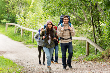 travel, tourism, hiking and people concept - group of happy friends or travelers with backpacks