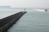 Sea near Vlissingen, Zeeland, Netherlands, old wooden pier at high tide and big cargo ship on horizon - 224907220