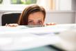 Leinwandbild Motiv Businesswoman Peeking Behind The Desk
