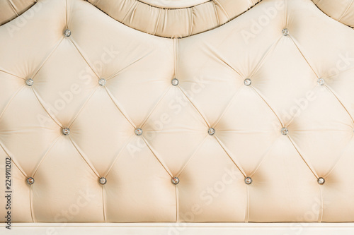 Beige Soft Textile Background With Symmetrical Buttons On The Corners Of  Diamonds. Soft And Expensive
