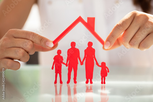 Businesswoman Protecting Family Figures With Roof - 224911479