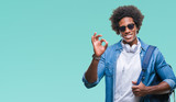 Afro american man wearing headphones and backpack over isolated background doing ok sign with fingers, excellent symbol - 224913481