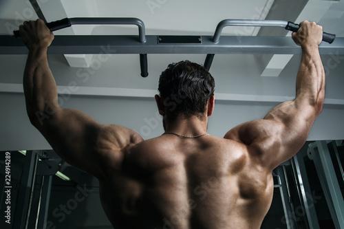 Biały model fitness mięśni człowieka wiszące na drążku, pokazując mu plecy