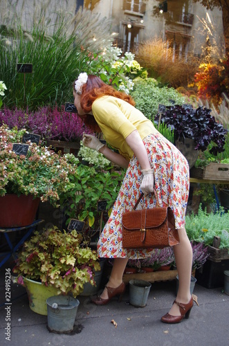 A woman smells and admires the flowers in the streets of Montmartre in Paris with the house facades in the background