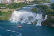 Niagara Falls over river with rocks and boat.