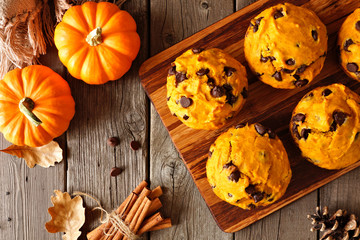 Autumn pumpkin chocolate chip muffins. Top view table scene on a rustic wood background.