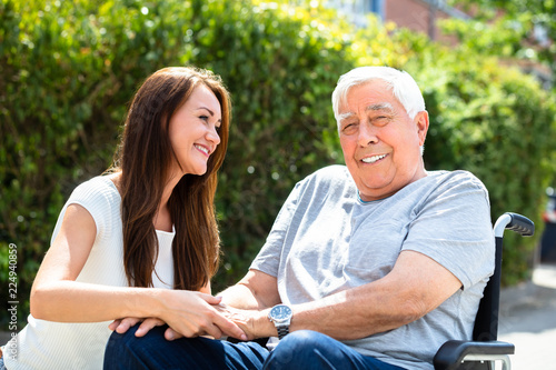 Woman Looking At Her Father Sitting On Wheelchair