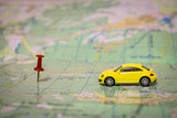 A yellow passenger car travels by geographic map. Route of movement on the world map. The concept of travel. Selective focus