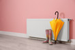 Leinwanddruck Bild - Modern radiator, rubber boots and umbrella near color wall with space for text. Central heating system