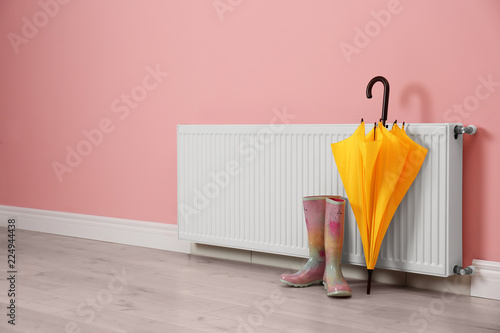 Leinwandbild Motiv Modern radiator, rubber boots and umbrella near color wall with space for text. Central heating system