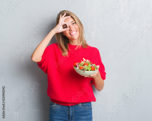 Leinwanddruck Bild Beautiful young woman over grunge grey wall eating tomato salad with happy face smiling doing ok sign with hand on eye looking through fingers