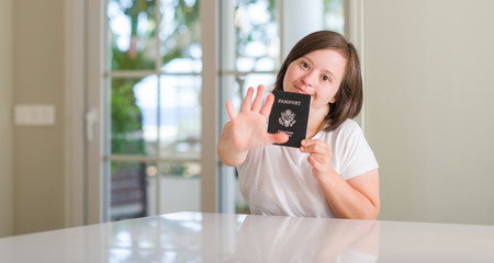 Down syndrome woman at home holding usa passport with open hand doing stop sign with serious and confident expression, defense gesture